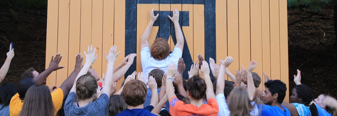 group of students lifting up another student to scale a wall