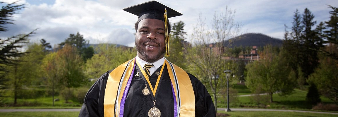Graduate in cap and gown with campus in the background